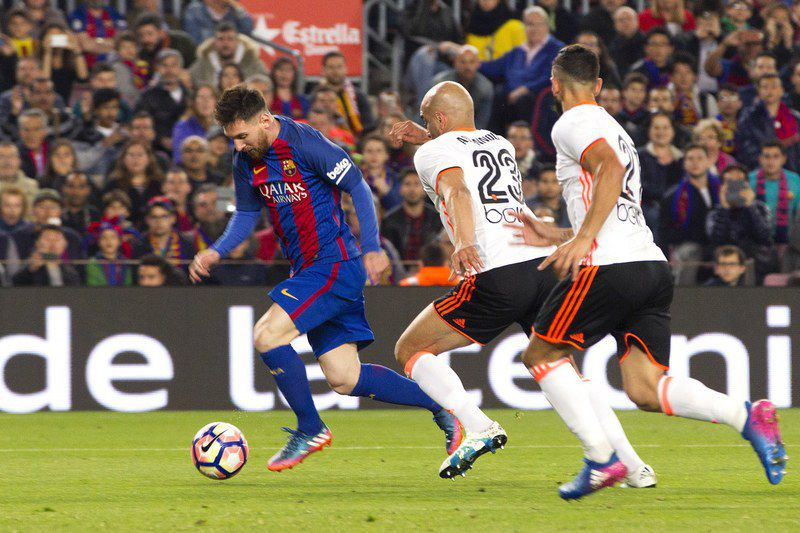 epa05858933 FC Barcelona´s Argentinian striker Leo Messi (L) escapes from Tunisian defender Aymen Abdennour (C) of Valencia CF to score his secong goal during their Spanish First Division soccer match played at Camp Nou stadium in Barcelona, 19 March 2017.  EPA/MARTA PEREZ