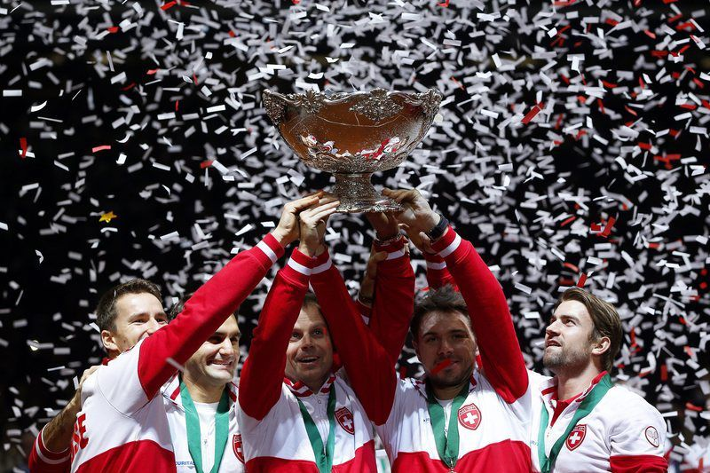 Suíça conquista a primeira Taça Davis • epaselect epa04500966 Swiss Davis Cup team players celebrate with the trophy after defeating France in the Davis Cup World Final at the Pierre Mauroy Stadium in Lille, France, 23 November 2014. Switzerland won 3-1.  EPA/YOAN VALAT