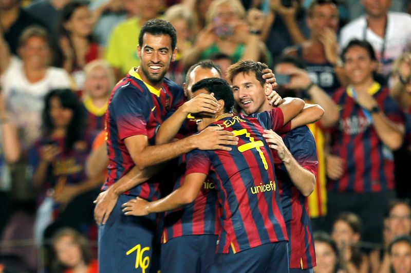 Barcelona's Argentinian forward Lionel Messi (R) celebrates his goal with Barcelona's midfielder Sergio Busquets (L) and teammates during the 48th Joan Gamper Trophy football match FC Barcelona vs Santos at the Camp Nou stadium in Barcelona on August 2, 2013.    AFP PHOTO/ JOSE JORDAN