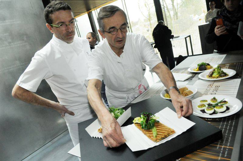 TO GO WITH AFP STORY BY EMMY VARLEY French chef Michel Bras and his son Sebastien present a dish at Bras' new restaurant in the Soulages museum in Rodez, southern France, on March 25, 2014. AFP PHOTO JOSE TORRES / AFP PHOTO / JOSE TORRES