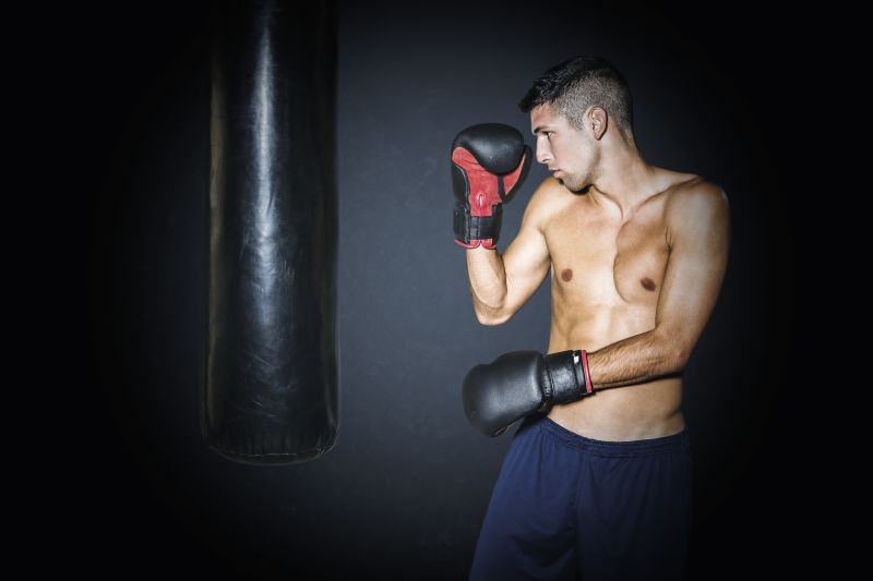Muscular man training with punching bag at gym