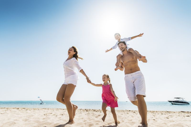 Low angle view of cheerful family enjoying at the beach. Man is carrying little boy on his shoulders.