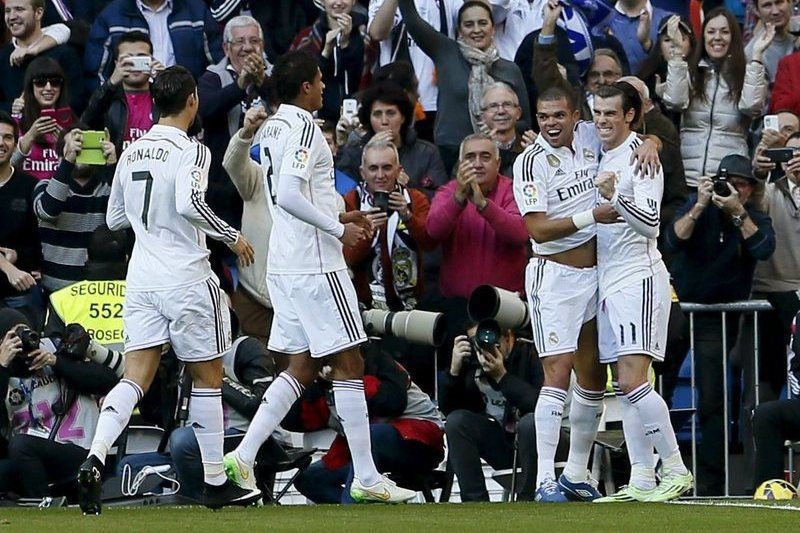 Gareth Bale celebra golo marcado com os colegas de equipa • Real Madrid's Welsh winger Gareth Bale (R) celebrates with Cristiano Ronaldo (L) , Varane (2-L) and Pepe (2-R) after scoring the 2-0 lead against RCD Espanyol during their Spanish Liga Primera Division soccer match played at Santiago Bernabeiu stadium in Madrid, Spain on 10 January 2015. • EPA/Juan Carlos Hidalgo