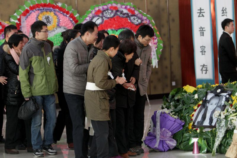 Family members and friends mourn during the funeral ceremony of Qiu Yuanyuan, a Chinese television presenter who died of cancer, in Zhengzhou, north China's Henan province on December 12, 2014. The fate of a Chinese television presenter, Qiu Yuanyuan, who died of cancer after refusing chemotherapy to save her unborn son sparked intense online debate on December 12. CHINA OUT AFP PHOTO