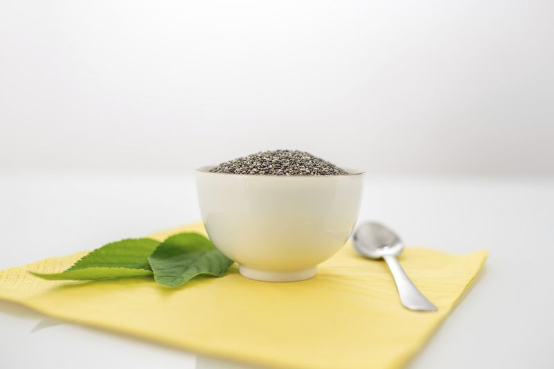 Bowl of dried chia seeds with fresh green leaves