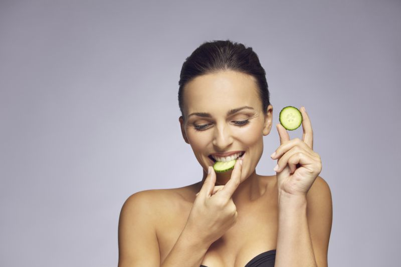 Attractive young woman eating a slice of cucumber