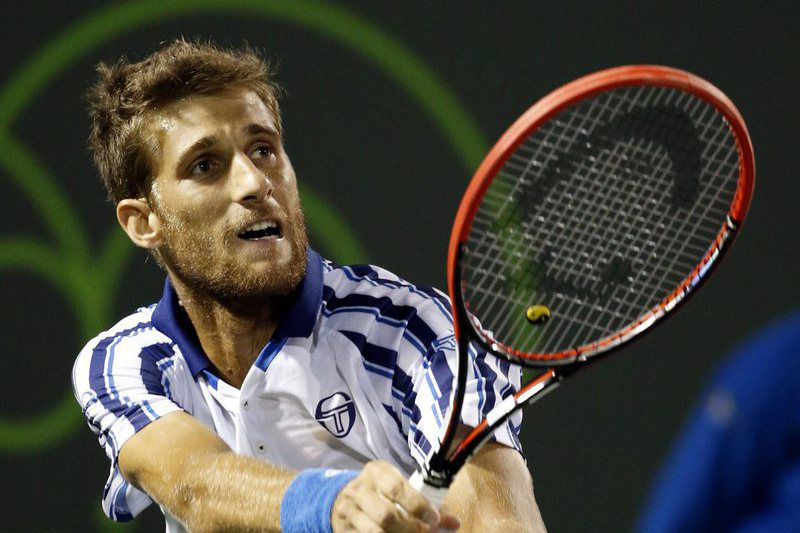 Martin Klizan em ação • epa04684482 Martin Klizan of Slovakia in action against Novak Djokovic of Serbia during their second round match at the Miami Open tennis tournament on Key Biscayne, Miami, Florida, USA, 28 March 2015. •  EPA/RHONA WISE