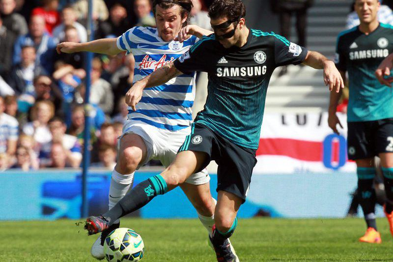 Joey Barton e Cesc Fabregas disputam a bola • QPR's Joey Barton (L) in action with Chelsea's Cesc Fabregas during the English Premier League soccer match between Queen's Park Ranger's and Chelsea at Loftus road in West London, England, 12 April 2015.  • EPA/SEAN DEMPSEY