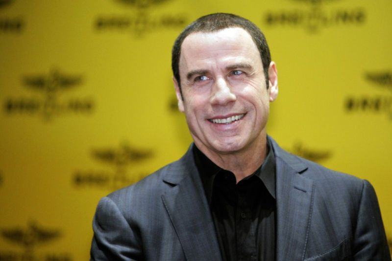 Actor John Travolta smiles before a news conference in Singapore July 30, 2012.  REUTERS/Tim Chong (SINGAPORE - Tags: ENTERTAINMENT)
