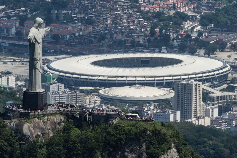 Estádio Maracanã, Rio de Janeiro • Aerial view of the Christ the Redeemer statue atop Corcovado Hill and the Mario Filho (Maracana) stadium in Rio de Janeiro, Brazil, on December 3, 2013. The Maracana stadium will host the Brazil 2014 FIFA World Cup and the 2016 Summer Olympics. AFP PHOTO / YASUYOSHI CHIBA • AFP
