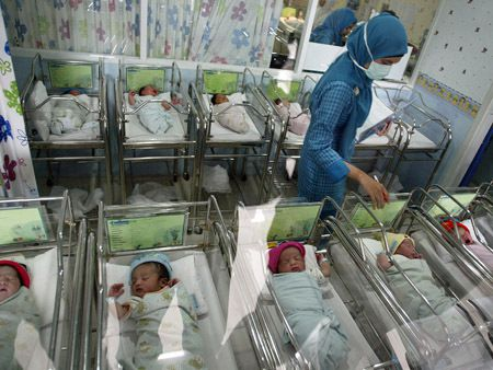 A nurse at the Mother and Child Hospital in Surabaya in East Java province looks after 13 newborn babies born on December 12, 2012. Several hospitals in Indonesia's main cities performed more Caesarians than usual with new mothers hoping a 12-12-12 birth date will bring luck to their newborns.     AFP PHOTO / JUNI KRISWANTO