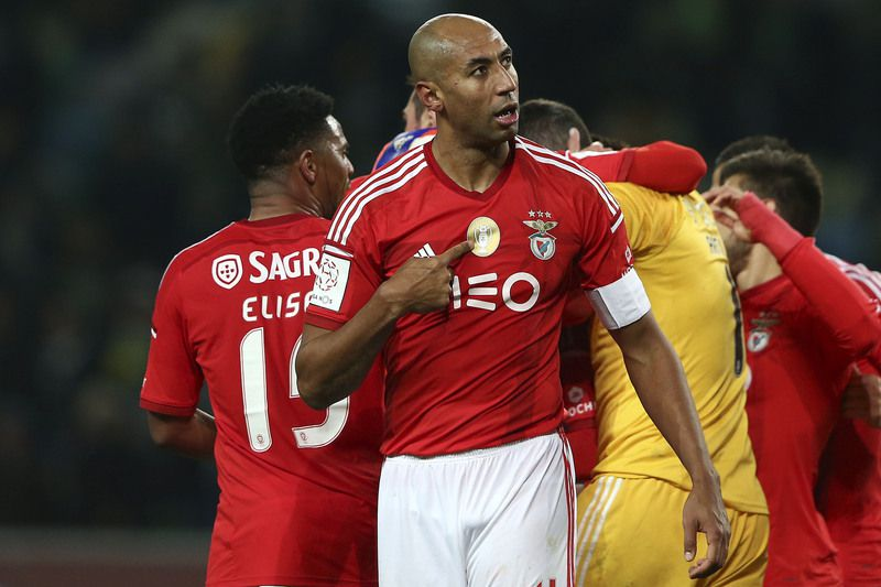 Sporting vs Benfica • Benfica's player Luisao points at the Champion symbol in his jersey as he looks to Sporting supporters at the end of their Portuguese First League soccer match held at Alvalade Stadium in Lisbon, Portugal, 08 February 2015. Benfica and Sporting tied 1-1. JOSE SENA GOULAO/LUSA • LUSA
