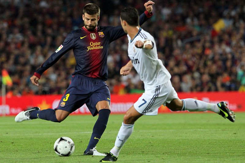 Barcelona's defender Gerard Pique (L) shoots past Real Madrid's Portuguese forward Cristiano Ronaldo during their Spanish Supercup first-leg football match FC Barcelona vs Real Madrid CF on August 23, 2012 at the Camp Nou stadium in Barcelona.     AFP PHOTO/ QUIQUE GARCIA