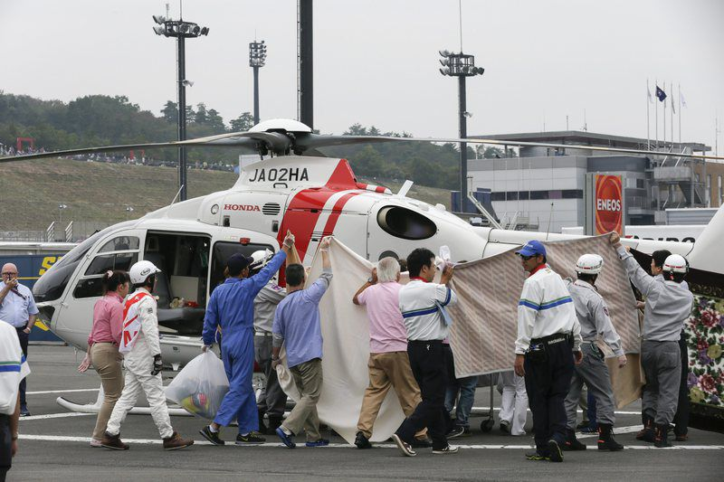 MotoGP motorcycling Grand Prix of Japan • epa04971500 Staff holds up blankerts to block the view of the media on Alex de Angelis of San Marino as he is carried to a helicopter after a heavy crash in the final practice session ahead of the official qualifying session of the MotoGP motorcycling Grand Prix of Japan at Twin Ring Motegi circuit in Motegi, north of Tokyo, Japan, 10 October 2015. De Angelis was taken by helicopter to the Dokkyo Hospital in Mibu for further examination and treatment and was reported to be conscious and breathing before being airlifted. The final race will be held on 11 October 2015.  EPA/KIMIMASA MAYAMA • Lusa