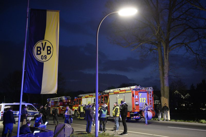 Police and firefighhters are seen near the site wher Borussia Dortmund's bus was damaged by an explosion some 10km away from the stadium prior to the UEFA Champions League 1st leg quarter-final football match BVB Borussia Dortmund v Monaco in Dortmund, western Germany on April 11, 2017. / AFP PHOTO / Sascha Schuermann • AFP or licensors