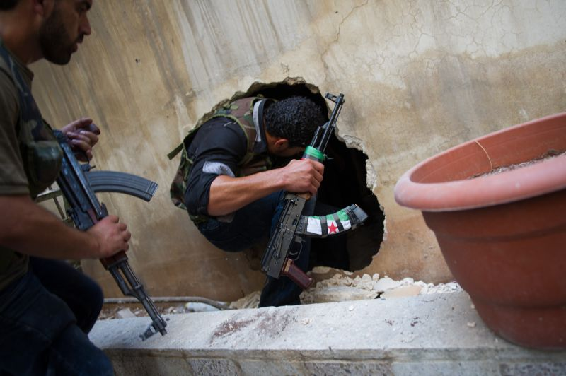 SYRIA, ALEPPO : A Syrian rebel from the Free Syrian Army (FSA) crawls through a hole in the side of a building in the Salaheddin district of the northern restive city of Aleppo on August 10, 2012. The FSA have created a series of hidden routes to combat positions in Salaheddine, where they continue to fight following a major offensive by the government army on the neighbourhood. AFP PHOTO/PHIL MOORE