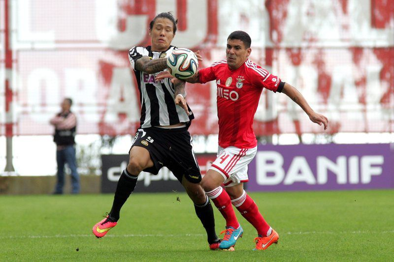Nacional x Benfica • epa04482848 Maxi Pereira (R) of Benfica fights for the ball with Suk of Nacional during their Portuguese First League soccer match held at Madeira Stadium, Funchal, Madeira Island, Portugal, 09 November 2014.  EPA/HOMEM DE GOUVEIA
