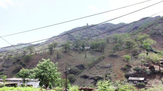 Árvores e montanhas verdes compõem a imagem.