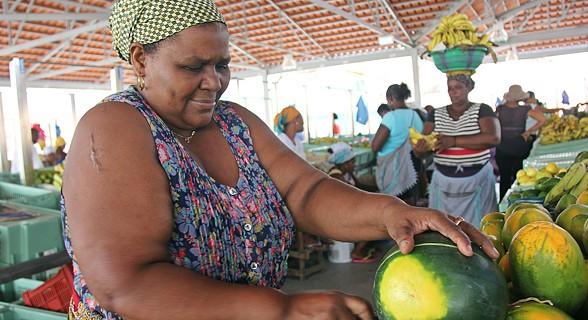 Mulher corta melancia para venda