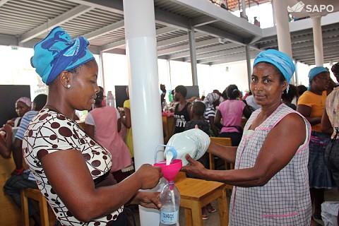Mulheres a encherem garrafas com leite de vaca
