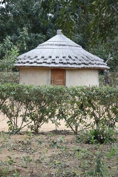 Cabana forrada a barro cor ocre coberta com telhado de makuti com rendilhados