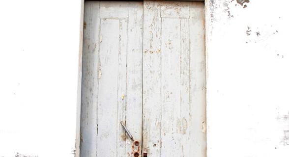 Entrada na torre faz-se por uma porta cinzenta de madeira