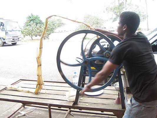 O jovem vai enfiando a cana-de-açúcar e com muita força, vai fazendo movimentos circulares enquanto a máquina esmaga a cana e do outro lado.