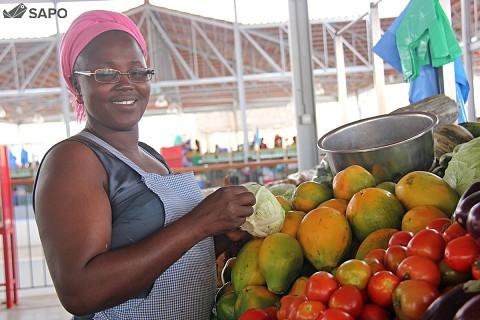 Vendedeira mostra frutas no seu posto de venda